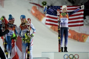 Gold medalist Mikaela Shiffrin of Colorado raises her flag as silver medalist Marlies Schild, center, and bronze medalist Kathrin Zettel, both of Austria, stand nearby after the second women's slalom run at the Sochi Winter Olympics on Friday, Feb. 21, 2014. (AAron Ontiveroz, The Denver Post)